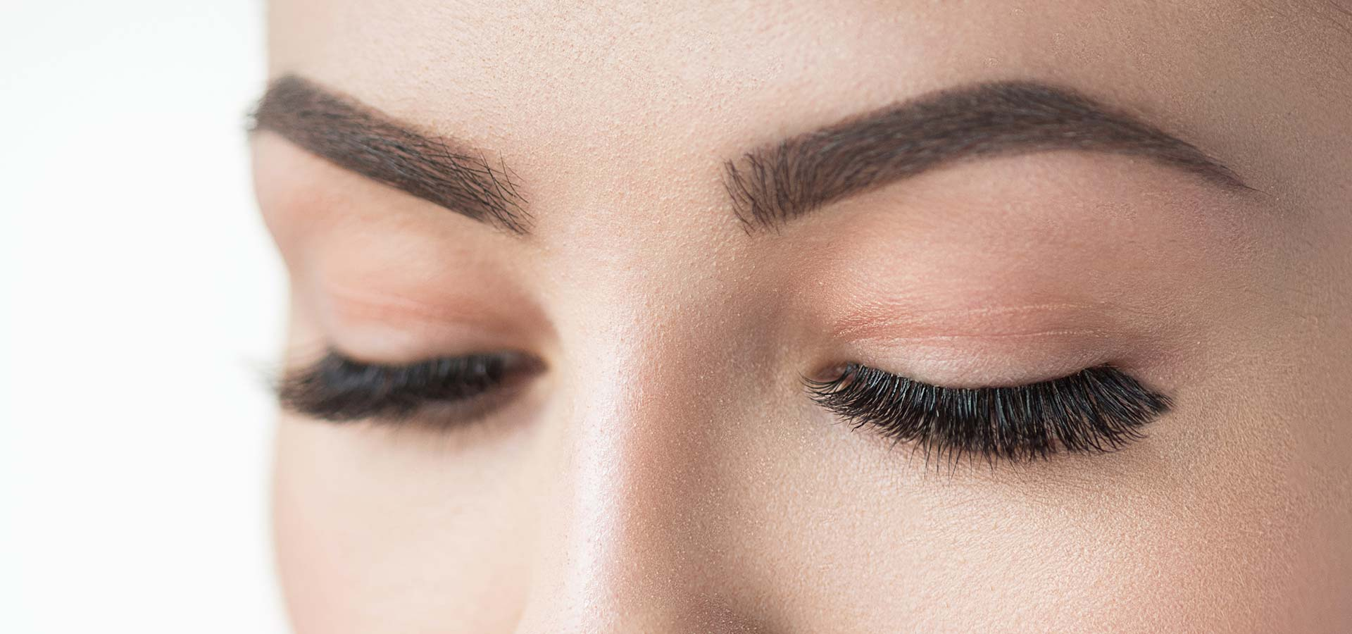 Close-up of closed woman's eyes and eyebrows.