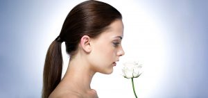 Woman smelling a white flower.