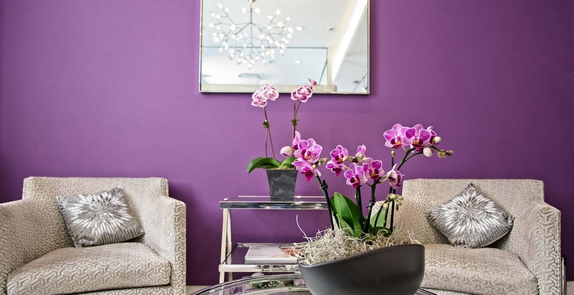 Maurice M. Khosh, MD, FACS office lobby. Purple walls, mirror, an orchid on a beautiful table.